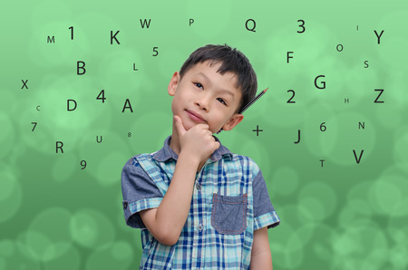 Asian schoolboy thinking on abstract green background