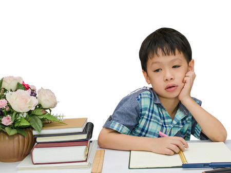 Asian schoolboy doing his homework on white background