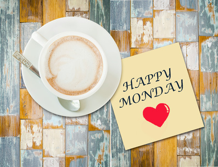 Coffee cup on wood table with paper note and message  Happy Monday