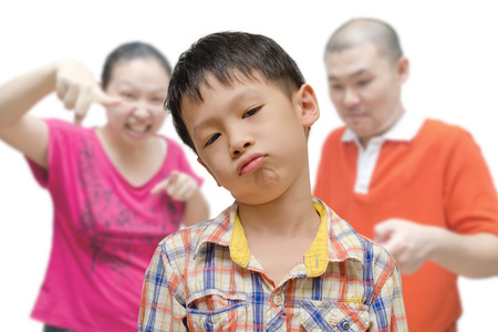 naughty child: Young Asian Boy Being Scolded by Parents  Stock Photo