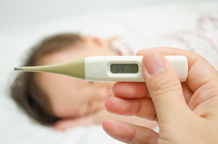 Mother holding thermometer foreground and sick little girl in bed