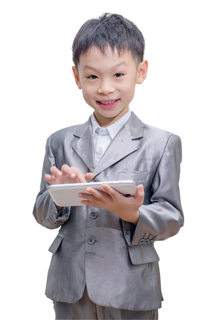 Asian boy in suit with tablet computer on white background photo