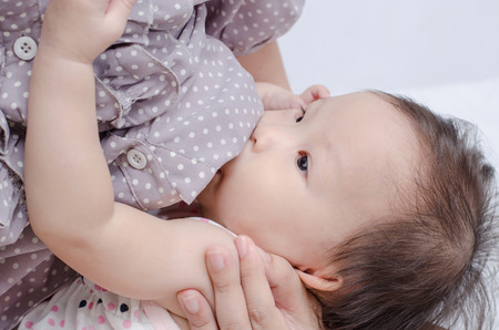 breasts girl: Asian mom breast feeding her baby girl  Stock Photo