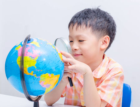 Asian boy looking map on globe via magnifying glass photo