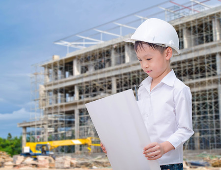 building, developing, construction and architecture concept - little boy with white helmet and blueprint.  photo