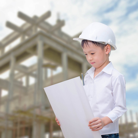 building, developing, construction and architecture concept - little boy with white helmet and blueprint.