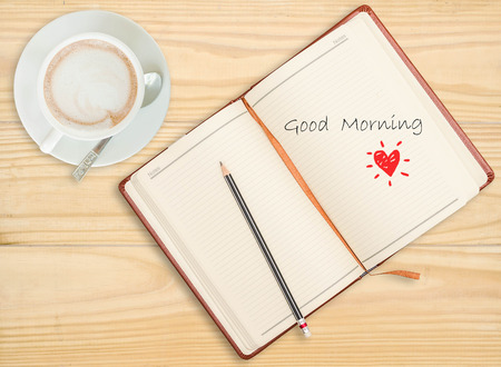 Good morning on notebook with pencil and coffee cup on wooden  photo