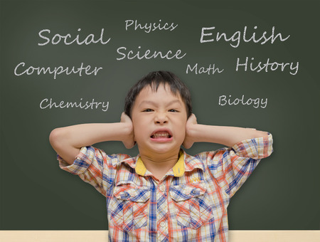 Young Asian student covering ears in front of chalkboard
