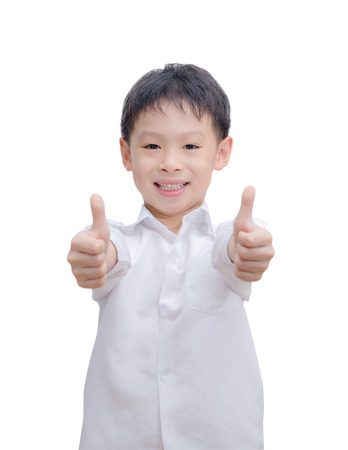 Portrait of beautiful little boy giving you thumbs up over white  photo