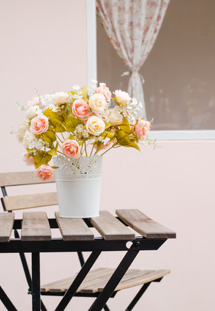 Decorative artificial roses flowers in basket photo
