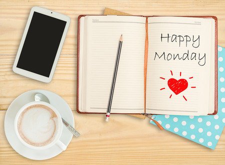 Happy Monday on notebook with pencil, smart phone and coffee cup  Stock Photo