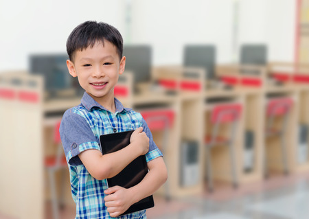 Asian boy with tablet computer in computer room smiling photo