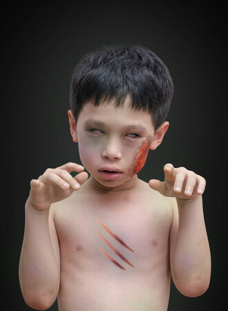Boy with halloween zombie make up over dark  Stock Photo