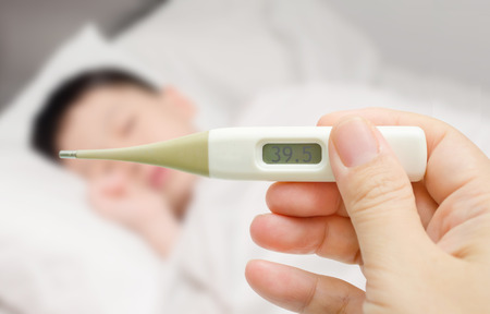 digital thermometer: Asian mother holding digital thermometer and her sick son  Stock Photo