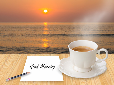 Coffee with Good morning on paper note in the beach