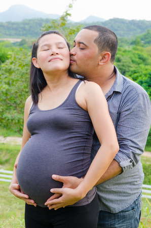 Pregnant wife and her husband in love outdoors photo
