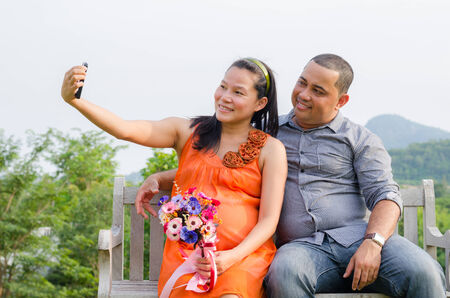 taking a wife: Pregnant Wife and Husband Taking Cell Phone Picture of Themselves At The Park Stock Photo
