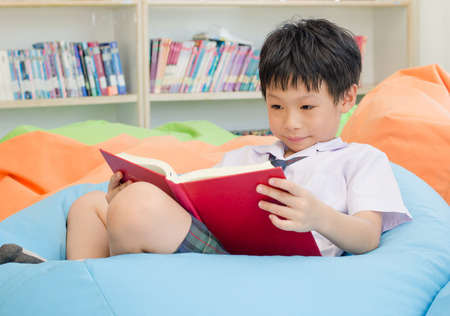 Asian schoolboy reading book in school library