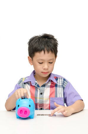 Asian smiling boy counting coins from his piggy bank isolated on white photo