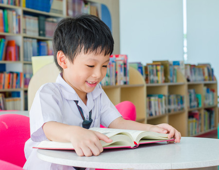 library student: Asian schoolboy reading book in school library