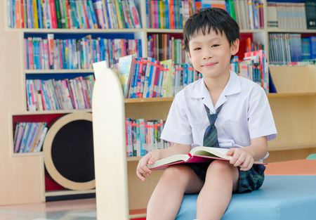 Asian schoolboy reading book in school library