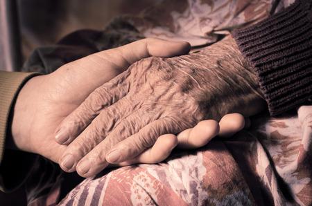 persona mayor: La mano de la chica joven toca la mano de la abuela