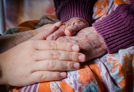 Young girl hand touch her grandma hand