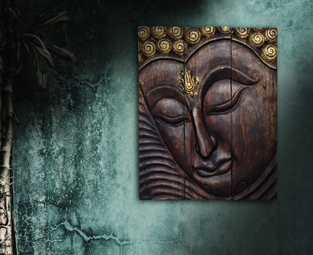 Buddha image in Thai style wood graving on the wall Stock Photo