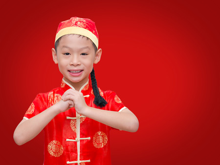 Asian boy with Chinese traditional dress holding ang pow or red packet monetary gift, Chinese new year concept. photo