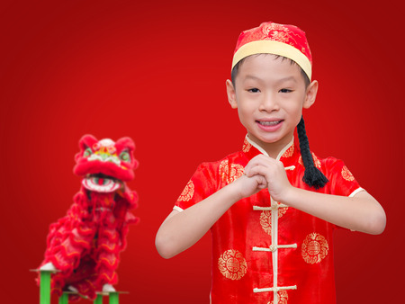 Happy Chinese new year.Young Asian boy with gesture of congratulation over red background. photo