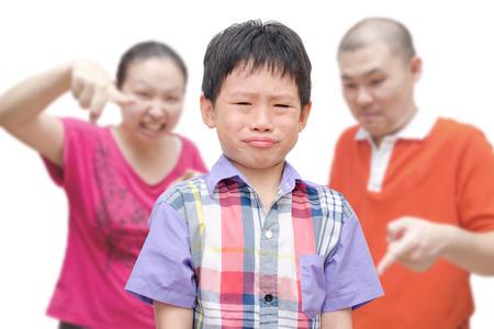 アジア系の若い親が彼を叱る間泣いています。