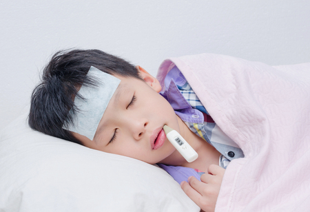 asian child: Little sick boy lying on bed with digital thermometer in mouth
