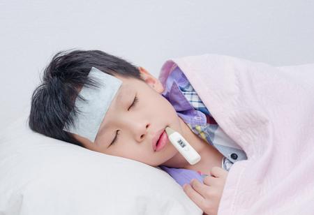 chory: Mała chorego chłopca leżącego na łóżku z cyfrowym termometrem w ustach