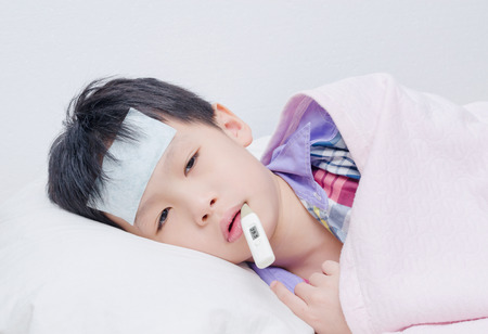Little sick boy lying on bed with digital thermometer in mouth