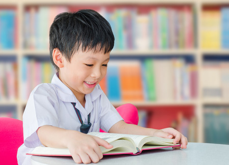 student in class: Asian boy student in uniform reading book in school library