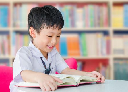 üniforma: Okul kütüphanesinde üniforma okuma kitabında Asya erkek öğrenci Stok Fotoğraf
