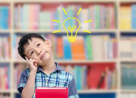 pensando: Muchacho asi�tico joven que piensa con el bulbo en la biblioteca