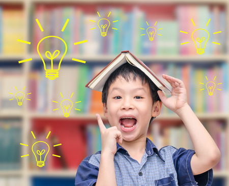 Young Asian boy thinking with light bulbs in library photo