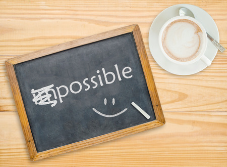 Change impossible to possible on chalkboard with coffee cup Stock Photo