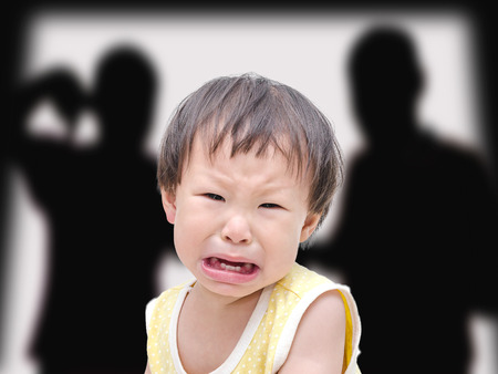 dysfunctional: Crying little asian girl with her fighting parents in the background