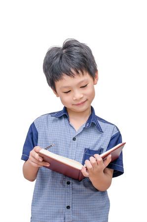 白い背景の上の本を読んで幸せなアジア少年