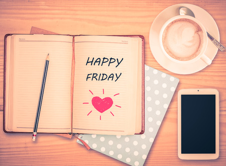 Happy Friday on notebook , pencil, smart phone and coffee cup with vintage filter