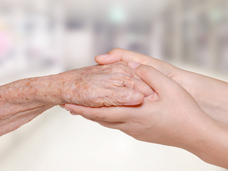 retiring: Young nurse holding old patient hand in hospital