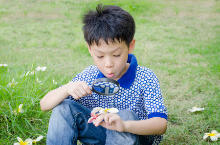 Asian boy exploring the environment with a magnifying glass photo