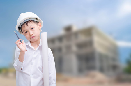 asian architect: building, developing, construction and architecture concept -little boy in white helmet thinking