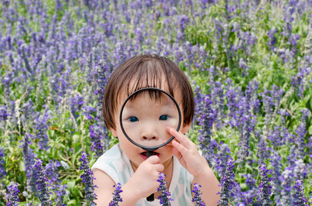 Little Asian girl with magnifying glass in flower field photo