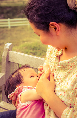 child girl nude: Asian mom breast feeding her baby girl in park with vintage filter