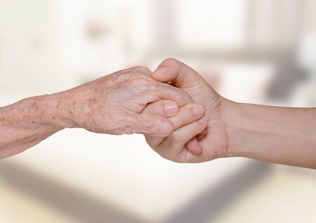 retiring: Young woman holding her grandma hand in bedroom