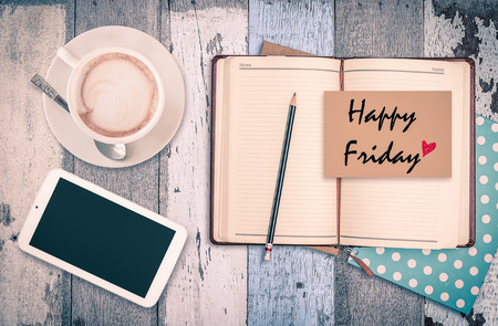 Happy Friday on notebook with smart phone and coffee cup on wood background