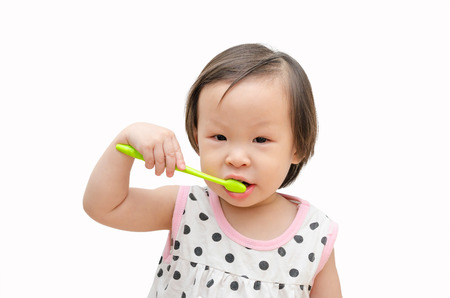 Little Asian girl cleansing her tooth by toothbrush over white background
